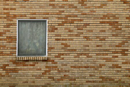 a single stained glass window on a colorful brick church wall