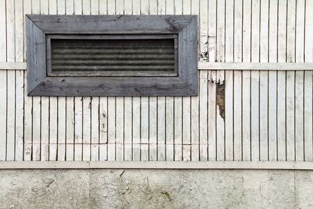 a small long boarded window on a white faded barn wall Stock Photo