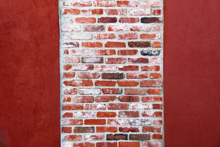 a bright red painted vintage brick garden wall column Stock Photo