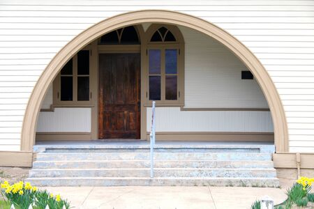 a vintage arched entrance with steps and garden featuring a retro wood door