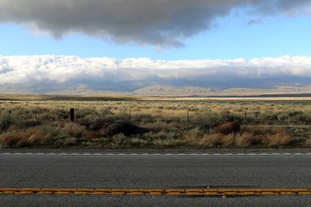 a dark desert road with distant mountains and storm clouds with shadows