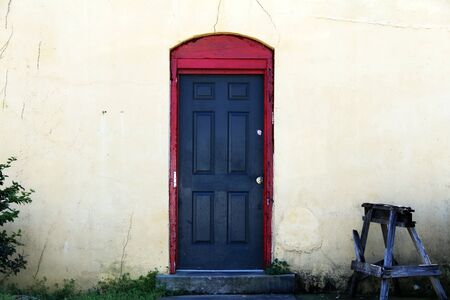 a black door with red trim at a vintage workshop entrance Stock Photo