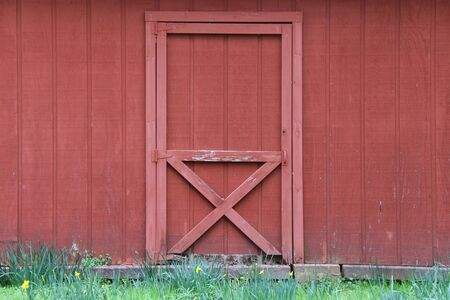 a red farm barn double door with grass path Stock Photo