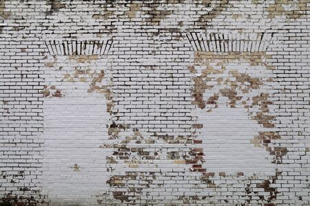 a brick wall with blocked windows painted white and faded Stock Photo