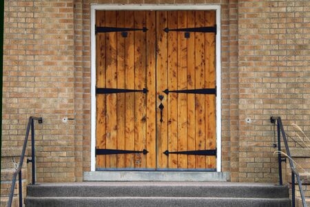 a pair of vintage iron hinge oak doors with brick entrance and steps
