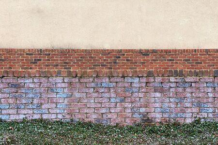 a retro colorful brick garden wall with grass path Stock Photo