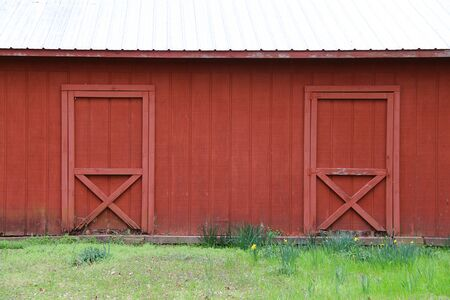 a painted red barn with white roof and double doors with grass field Stock Photo