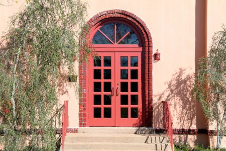 a retro building with bright red arched door entrance and steps Stock Photo