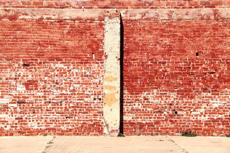 a bright sunlit vintage red brick building wall and sidewalk with shadows
