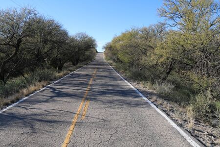 an old cracked two lane desert road leading into the horizon Stock Photo
