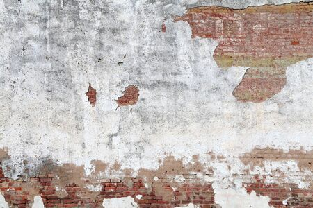 a faded white cracked stucco and red brick garden wall