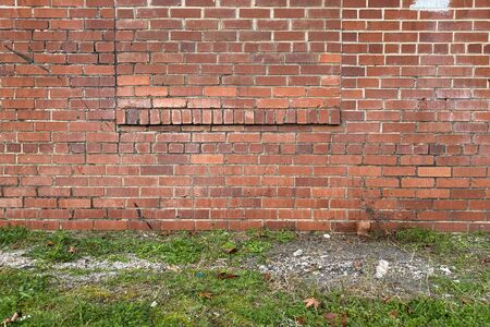 an ornate red brick back garden wall with grass patch path Stock Photo