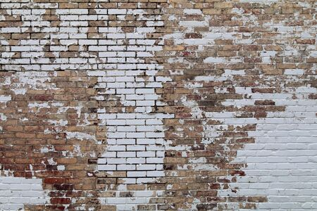 the peeling paint off a vintage old brick garden wall