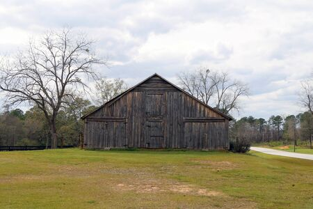 a cloudy sky with a vintage old barn with grass field Stock Photo