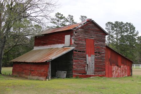 a vintage old red country farm barn in a grass field