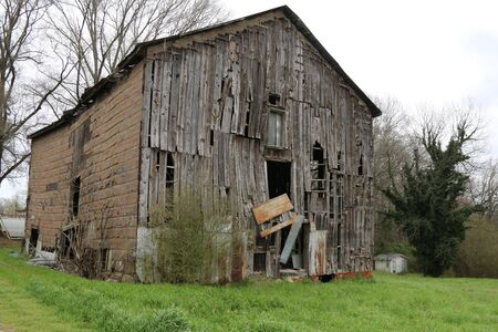 a large falling apart old farm barn that is rundown and abandoned