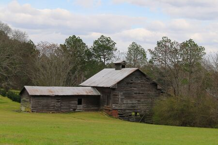 an old vintage riverbank country farm barn building with sunny and cloudy sky