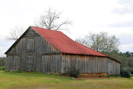 a retro farm barn with a red roof in an empty field