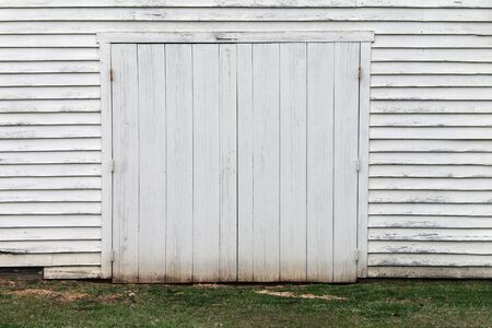 a faded white wooden warehouse building doorway and grass Stock Photo