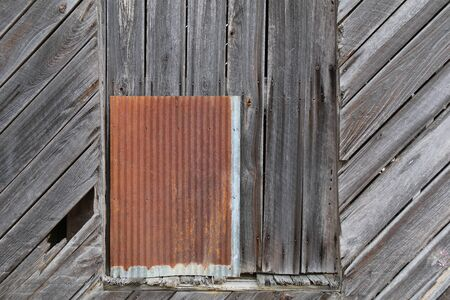 a retro old wood warehouse wall with rusted metal window Stock Photo
