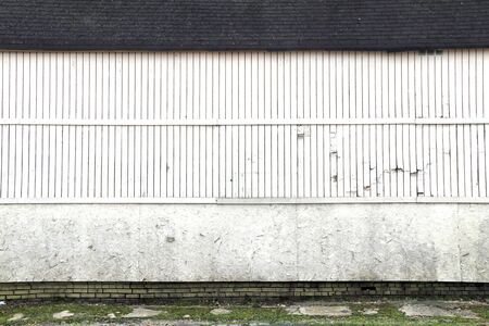 a vintage faded white wooded warehouse building wall with roof line and grass
