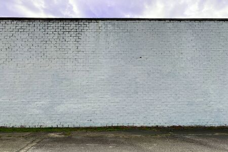 a white faded stone brick factory warehouse wall in an alley