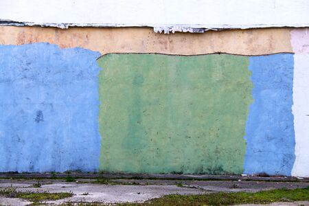 a colorful green and blue painted old factory warehouse wall in an alley Stock Photo