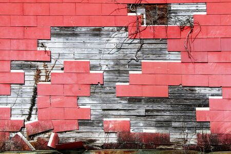 a cracked red shingle tile warehouse wall exposed rotten wood