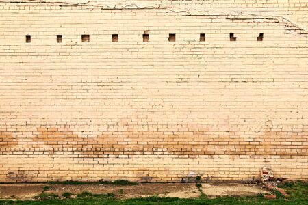 a faded weathered painted stone brick warehouse wall