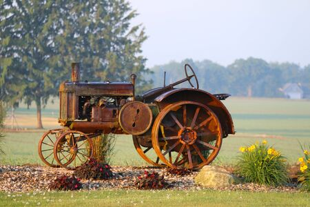 a rusty vintage farm tractor on display in a rural farm with bright flowers early morning