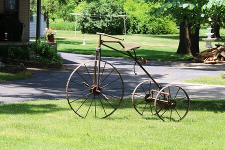 a vintage antique rusty three wheel bicycle bike trike parked on a grass lawn Stock Photo
