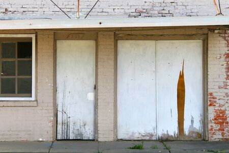 an abandoned boarded up storefront shop with white painted brick and damaged awning