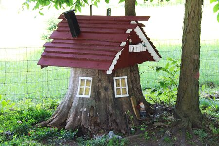 a beautiful old rustic stump for elf and gnome hut house in a country field  Stock Photo
