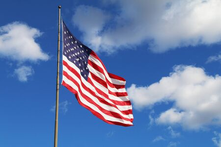 a bright flowing waving american flag on a sunny day with a few white clouds Reklamní fotografie