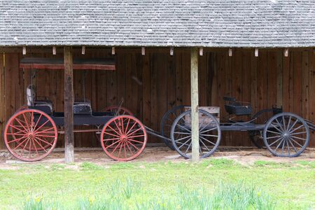 two beautiful vintage horse cart trap vehicle next to a rustic barn stable building