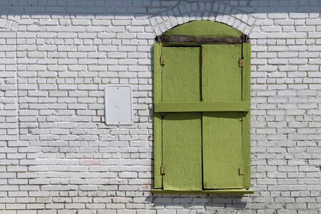 a bright green shutter window against a bright white brick wall 스톡 콘텐츠