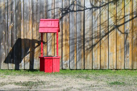 a very bright red wishing water well in front of a brown fence and grass Stock Photo