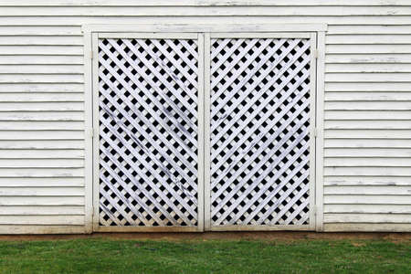 a white factory building barn with lattice wood door and grass Stock Photo