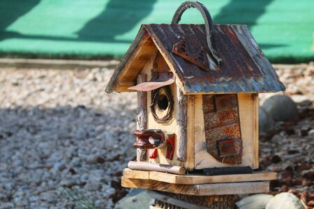 a unique rustic hand made tin roof birdhouse on a rock ground