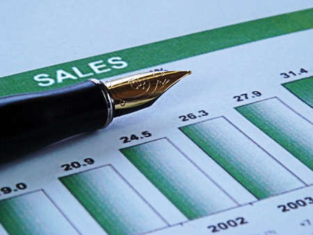 future earnings: close-up of a pen on top of a financial graph showing sales growth