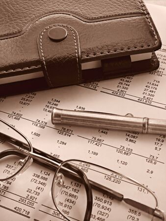 close-up of an organizer, a pen and glasses on top of financial statements