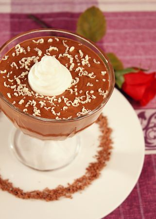Chocolate mousse in coctail glass on a white plate with rose and purple table cloth Stock Photo