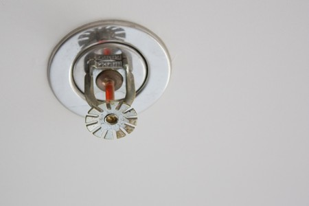 fire detector and extinguisher with black ceiling as background Stock Photo