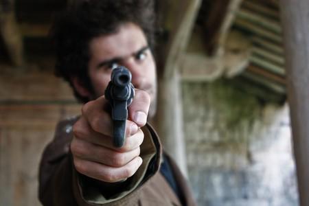 attacker: Man pointing gun at viewer