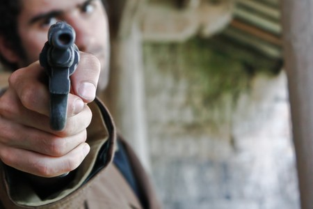 assailant: Man pointing gun at viewer - with copy space Stock Photo