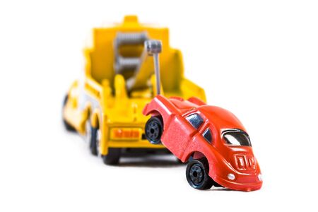 tow: Red car being towed away by yellow tow truck (2)