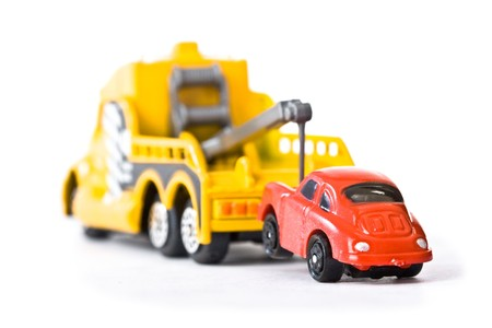 tow truck: Red car being towed away by yellow tow truck (1)