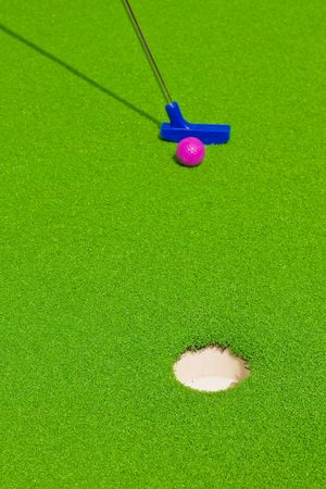 golf club aiming to score ball in hole