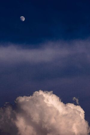 moon and clouds in blue sky at dusk photo