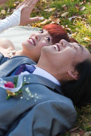 smiling bride and groom lying on ground in park photo